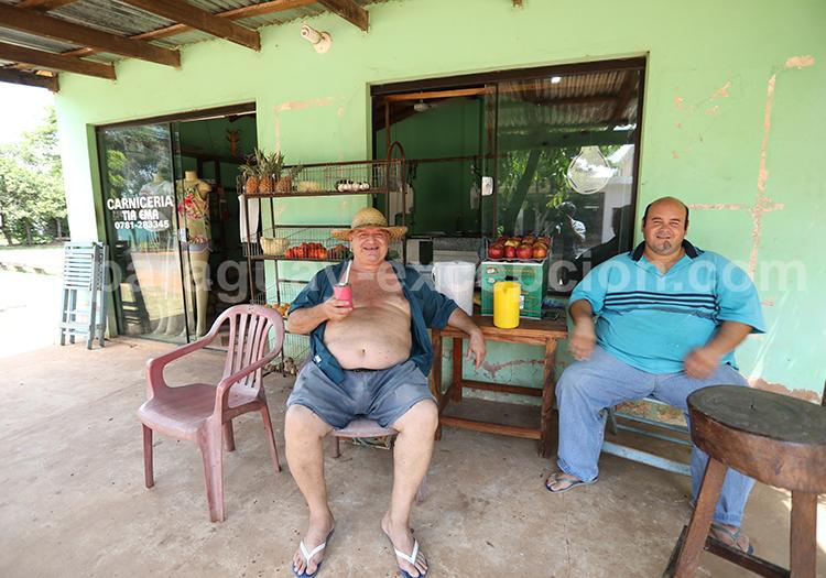 Hommes assis devant leur commerce à Santa Maria de Fe, Yvy, Paraguay